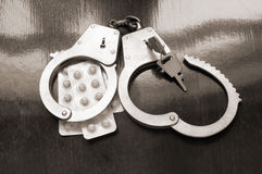 Handcuffs and tablets Stock Photo