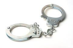 Handcuffs tegen witte achtergrond stock foto