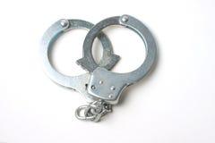 Handcuffs tegen witte achtergrond Stock Foto's