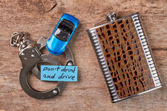 Handcuffs, toy car, message, hip flask. Stock Photography