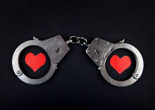 Handcuffs and Two Hearts. On the Black Background Stock Images