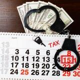 Handcuffs van de staalpolitie, dollarsgeld, 15 April op kalender en Stock Afbeeldingen