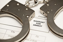 Handcuffs on a warrant for arrest. Royalty Free Stock Photo