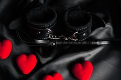 Handcuffs and whip for BDSM sex with red hearts. The concept of passionate love and hard sex on Valentine`s day stock photography