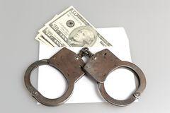 Handcuffs and white envelope with money on gray. Background Royalty Free Stock Photography