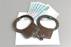 Handcuffs and white envelope with money on gray. Background Royalty Free Stock Photos