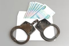 Handcuffs and white envelope with money on gray. Background Stock Photo