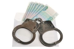 Handcuffs and white envelope with money on white background Royalty Free Stock Photo