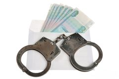 Handcuffs and white envelope with money on white background Royalty Free Stock Image