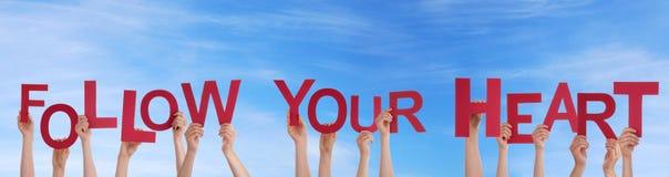 Handdas halten folgen Ihrem Herzen im Himmel Lizenzfreie Stockfotografie