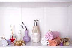 Handdoeken in een houten dienblad met aromaeetstokjes, kaarsen, zeeschelpen, massagewashandjes en een fles met een automaat Royalty-vrije Stock Foto