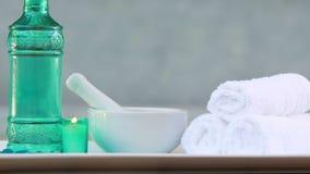 Handdoeken en glasfles met kaars en mortier en stamper stock footage