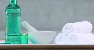 Handdoeken en glasfles met kaars en mortier en stamper stock video