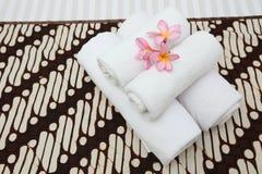 Handdoeken op het bed van de batikdekking stock foto's