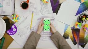 Handdraufsicht Frauendesigner, der ihren Smartphone mit gr?nem Schirm in der Tabelle, Bl?tternnachrichten, Fotos verwendet stock video