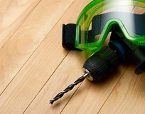 Handdrill and goggles. On wooden background Royalty Free Stock Image