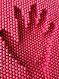 Handdruk op de rode speldenstuk speelgoed achtergrond Stock Foto's