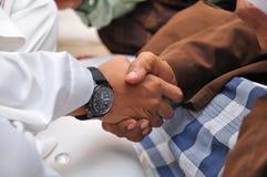 Handdruk tussen de jonge en oude mens Stock Afbeelding