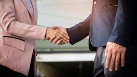 Handdruk van de close-up de vriendschappelijke vergadering tussen bedrijfsvrouw en B Stock Foto
