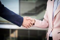 Handdruk van de close-up de vriendschappelijke vergadering tussen bedrijfsvrouw en B Stock Foto's