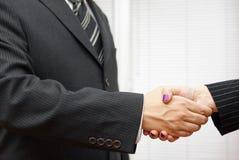 Handdruk van partners, de mens en vrouw in het bureau Stock Afbeeldingen