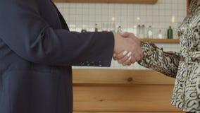 Handdruk van twee onderneemsters op vergadering in koffie stock video