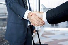 Handdruk van zakenlieden bij de luchthaven - bedrijfsreisconcept Stock Foto's
