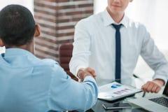 Handdrukcollega's wanneer het bespreken van de financiële overeenkomst T royalty-vrije stock afbeeldingen