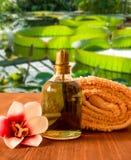 Handduk, flaska med olja och orkidéblomma royaltyfri fotografi