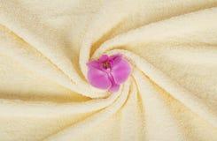 Handduk med en orkidéblomma Arkivfoton