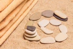 Handduk med kiselstenar på sanden Arkivbild