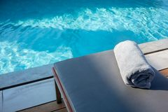 Handduk på att koppla av pölsäng bredvid simbassäng royaltyfria foton