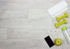 Handduk, vikter, vattenflaska, äpple och telefon på träbakgrund Royaltyfri Foto