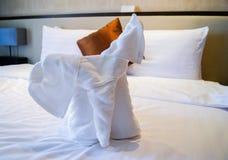 Handdukar i form av elefanter på ett bekvämt mjukt för vit säng Hemslöjder i handdukhotell behandla som ett barn elefanttrasor i  fotografering för bildbyråer