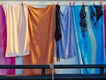 Handdukar och badningbaddräkter som torkar på klädstrecket Royaltyfri Bild