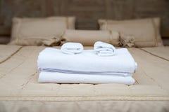 Handdukar på hotellsäng Arkivfoton
