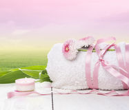 handduken som binds med det rosa bandet med tusenskönan, blommar sommarmorgonbakgrund Arkivfoto