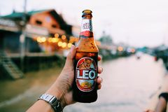 Handed bottle of cold Leo beer stock images