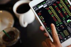Handel auf der Tablette mit dem erfahrenen Arbeiter on-line machen stockfotos