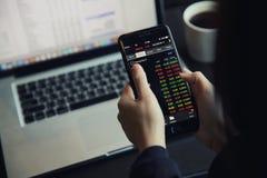 Handel online auf Smartphone und Notizbuch mit der Geschäftsfrauhand lizenzfreie stockfotografie