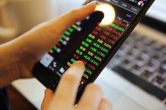 Handel online auf Smartphone und Notizbuch mit der Geschäftsfrauhand stockbild