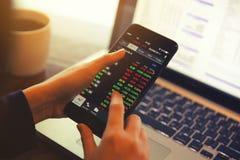 Handel online auf Smartphone und Notizbuch mit der Geschäftsfrauhand stockfotos