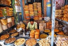 Handelaar binnen een snoepjesopslag die smakelijke koekjes en snacks verkopen Stock Foto's