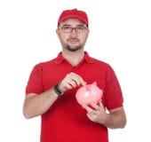 Handelaar die met moneybox een muntstuk opneemt Stock Foto's
