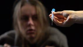 Handelaarshand die spuit met dosis aanbieden aan vrouw met terugtrekking, verslaving stock video