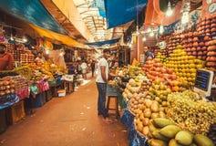 Handelaren van exotische tropische vruchten gemaakt tot kleurrijke showcases op stadsmarkt Stock Afbeeldingen