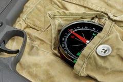 Handeldvapen och kompass på den red ut ryggsäcken Arkivfoton