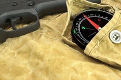 Handeldvapen och kompass på den red ut ryggsäcken Arkivbilder