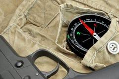 Handeldvapen och kompass på den red ut ryggsäcken Arkivbild