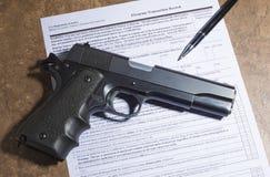 handeldvapen 1911 och penna med skjutvapenköpskrivbordsarbete Fotografering för Bildbyråer